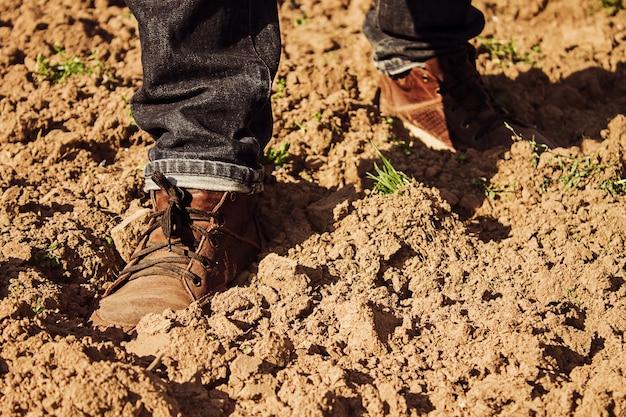 L'uomo sta camminando sul campo arato