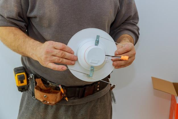 L'uomo sta installando la luce elettrica nel soffitto sostituendo i lavori di riparazione nell'appartamento.
