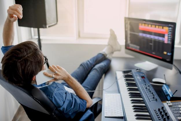 L'uomo sta lavorando al mixer audio in studio di registrazione o il dj sta lavorando in studio di radiodiffusione. l'industria musicale.