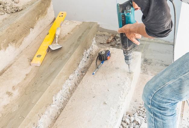 L'uomo sta lavorando con il rafforzamento della modifica della struttura delle scale in calcestruzzo usando un trapano a mano