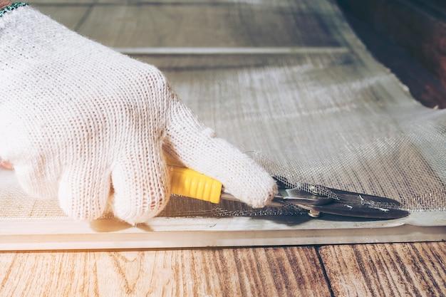 L'uomo sta lavorando con l'installazione di zanzariera