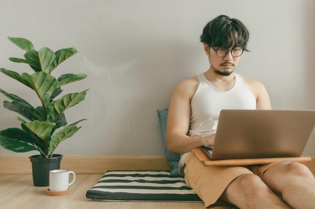 L'uomo sta lavorando nel suo salotto del suo appartamento nel concetto di lavoro da casa.