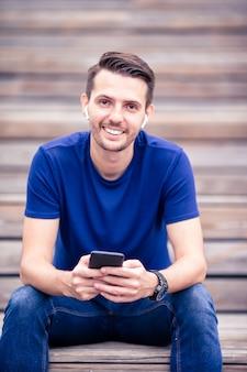 L'uomo sta leggendo il messaggio di testo sul cellulare mentre si cammina nel parco