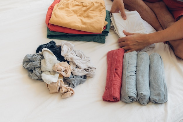 L'uomo sta piegando e sistemando i vestiti sul letto.
