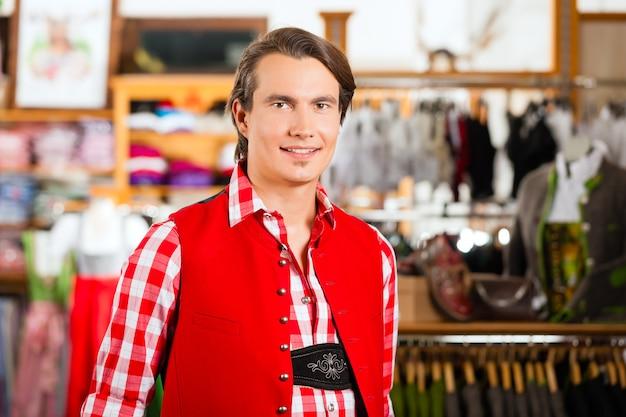L'uomo sta provando tracht o lederhosen in un negozio