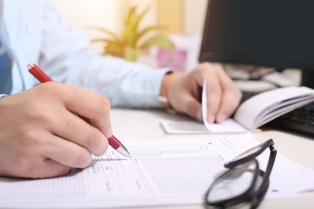 L'uomo sta riempiendo i documenti con la penna