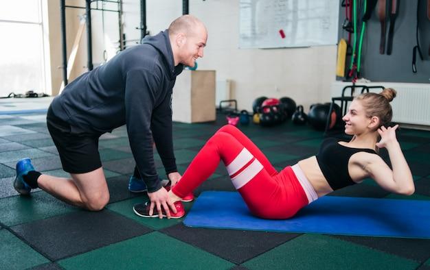 L'uomo sta tenendo le gambe della donna che sta facendo l'esercizio di torsione per i muscoli addominali sdraiato sul tappetino in palestra.