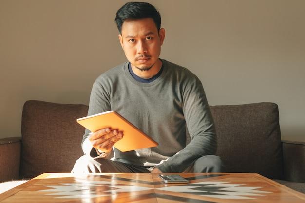 L'uomo sta usando il suo dispositivo tablet intelligente nel suo appartamento del salotto.