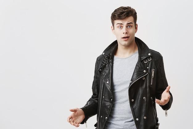 L'uomo stupido con un taglio di capelli elegante vestito con una giacca di pelle nera sembra stupito, stupito dalle notizie negative. ragazzo hipster emotivo esprime sorpresa, non crede ai suoi occhi.