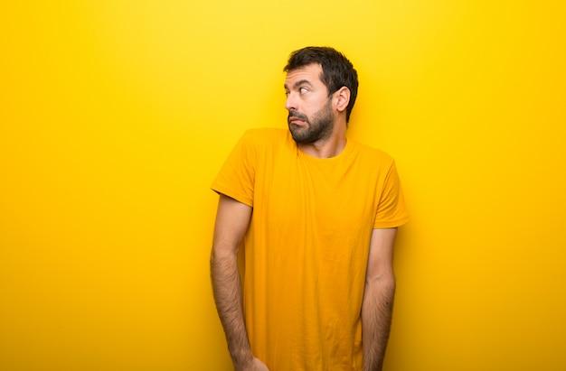 L'uomo su un colore giallo vibrante isolato è un po 'nervoso e spaventato premendo i denti