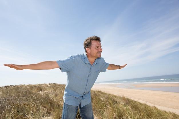 L'uomo sulla spiaggia arma su, concetto di vacanza di libertà