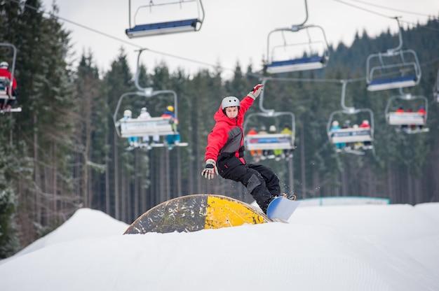 L'uomo sullo snowboard salta su un ostacolo