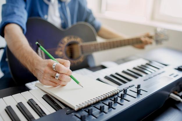 L'uomo suona la chitarra e produce colonne sonore elettroniche