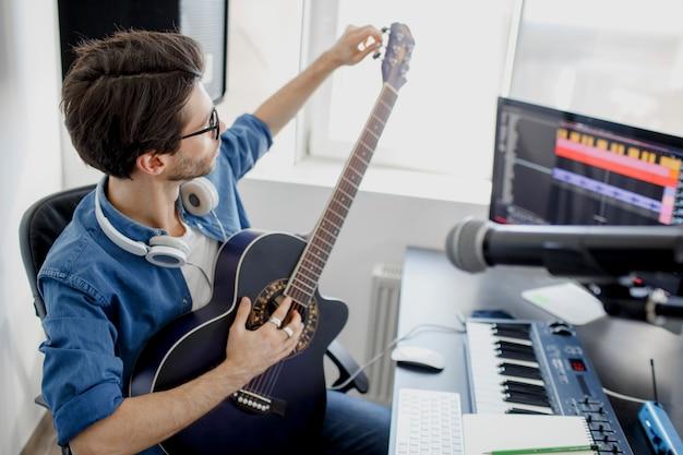 L'uomo suona la chitarra e produce colonne sonore o tracce elettroniche nel progetto a casa. arrangiatore di musica maschile che compone canzone sul piano midi e apparecchiature audio in studio di registrazione digitale.