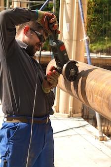 L'uomo taglia i prodotti flessibili in acciaio