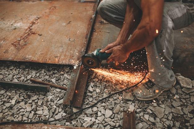 L'uomo taglia il ferro per strada.