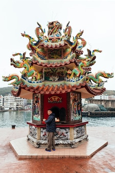 L'uomo taiwanese locale guarda la telecamera mentre brucia joss paper all'interno del santuario cinese nel villaggio di pescatori di yehliu.
