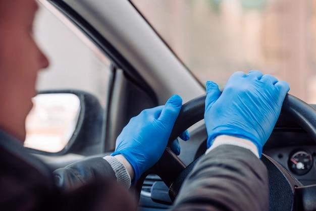L'uomo tiene il volante di un'auto in guanti medici protettivi. primo piano delle mani guida sicura in taxi durante il coronavirus pandemico. proteggere guidatore e passeggeri da batteri e infezioni da virus.