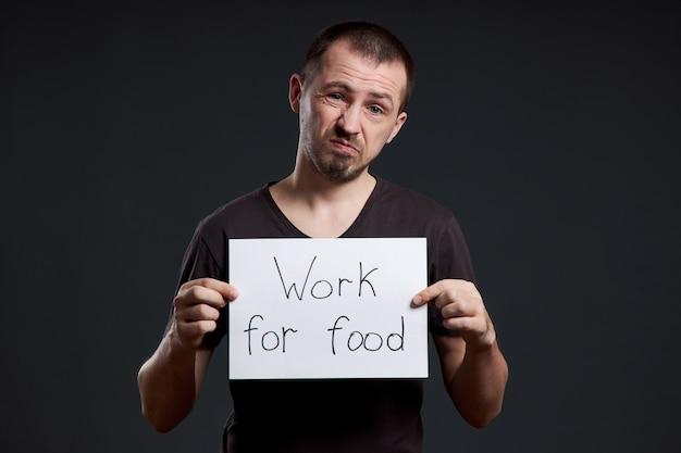 L'uomo tiene in mano un foglio di carta per poster con la scritta i work for food. sorriso e gioia, posto per il testo, copia spazio