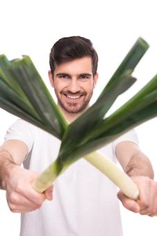 L'uomo tiene la cipolla verde in mano e sorride.