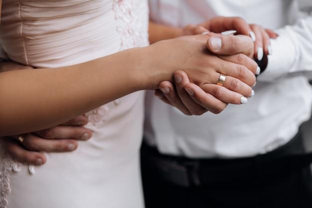 L'uomo tiene la mano della donna tenera nel suo forte braccio