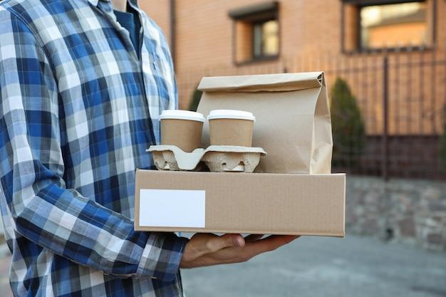 L'uomo tiene la scatola vuota, tazze di caffè e pacchetto di carta all'aperto
