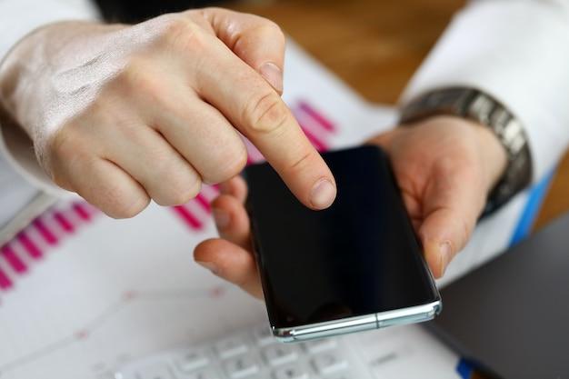L'uomo tiene smartphone appoggiato sul rapporto finanziario