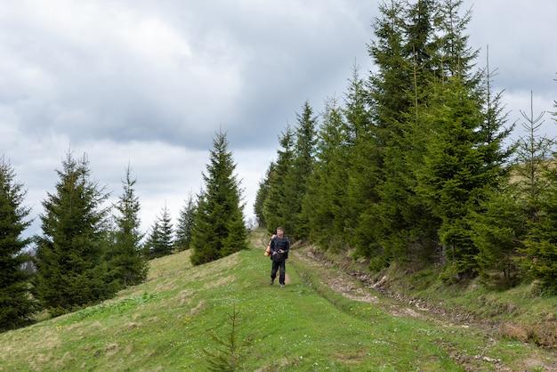 L'uomo turistico cammina nella foresta con una macchina fotografica in sue mani