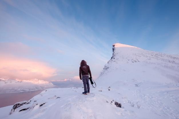 L'uomo turistico si arrampica sulla montagna nevosa superiore