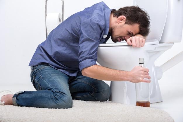 L'uomo ubriaco con il vino imbottiglia la toilette, isolata