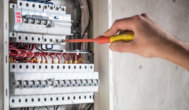L'uomo, un tecnico elettrico che lavora in un centralino con micce. installazione e collegamento di apparecchiature elettriche.