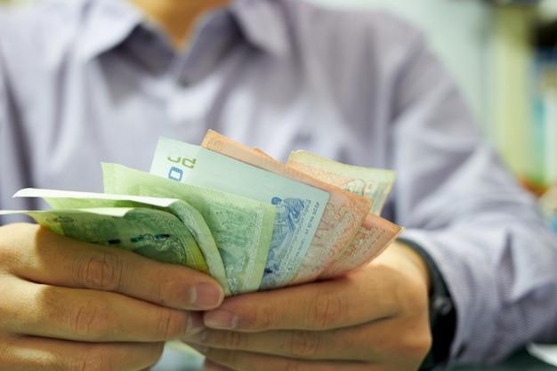 L'uomo uniforme sta contando la banconota dei soldi per il concetto di problema di crisi economica
