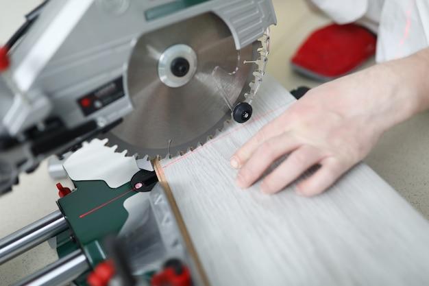 L'uomo usa il tavolo da sega circolare mentre taglia il laminato