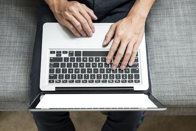 L'uomo usa laptop sul divano in casa sua. veduta dall'alto, concetto di lavoro a casa