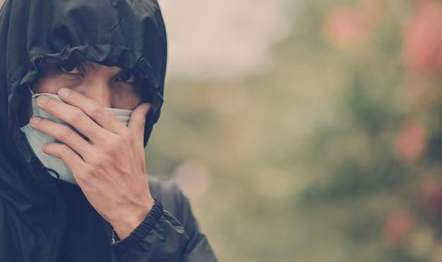 L'uomo usa maschera chirurgica e cappuccio nero