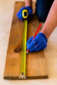 L'uomo utilizza la misura di nastro su legno