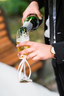 L'uomo versa il champagne nel bicchiere