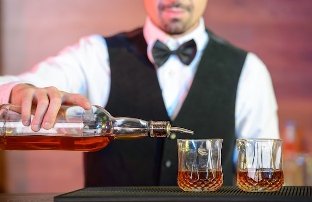 L'uomo versa l'alcool in bicchieri al bar.