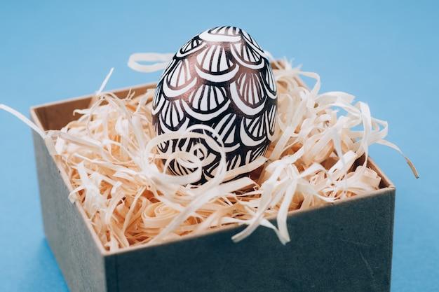 L'uovo di pasqua è dipinto in bianco e nero, l'astrazione, si trova nella scatola, all'interno della quale sono trucioli di legno. uovo di pasqua dipinto su uno sfondo blu. avvicinamento