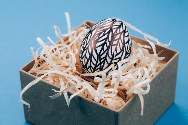 L'uovo di pasqua è dipinto in bianco e nero, un'astrazione, si trova in una scatola.