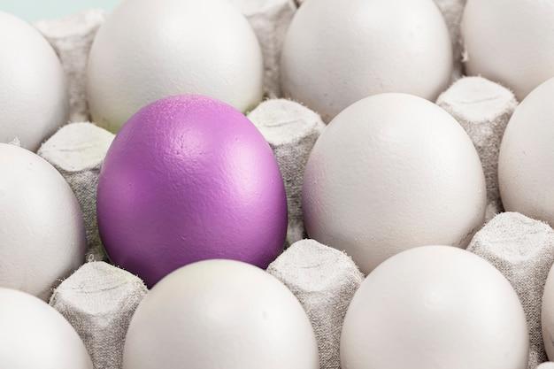 L'uovo di pasqua viola si distingue tra quelli bianchi, in una scatola da vicino, simbolo di individualità. concetto per la pasqua
