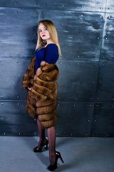 L'usura bionda elegante della ragazza sulla pelliccia e sul vestito combi hanno posato contro la parete d'acciaio sullo studio.