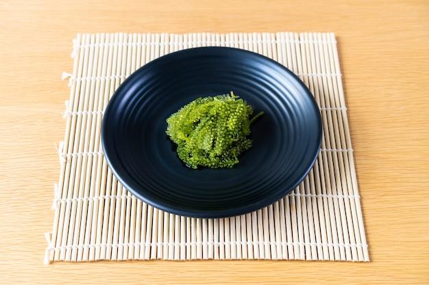 L'uva naturale del mare si chiude su servito nel piatto di pietra nero di lusso nel ristorante giapponese.