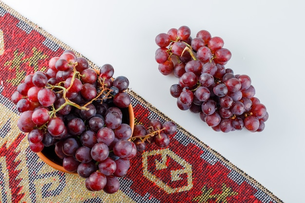 L'uva rossa in una ciotola si trovava sul tappeto bianco e tradizionale