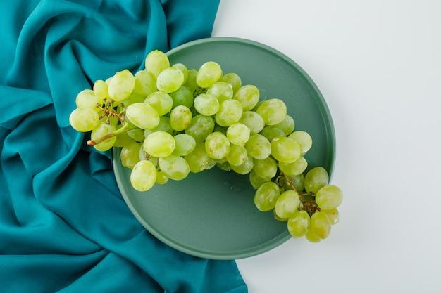 L'uva verde in un piatto piatto giaceva su bianco e tessuto