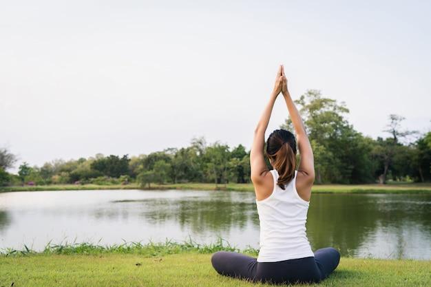 L'yoga della giovane donna asiatica all'aperto mantiene la calma e medita mentre pratica l'yoga