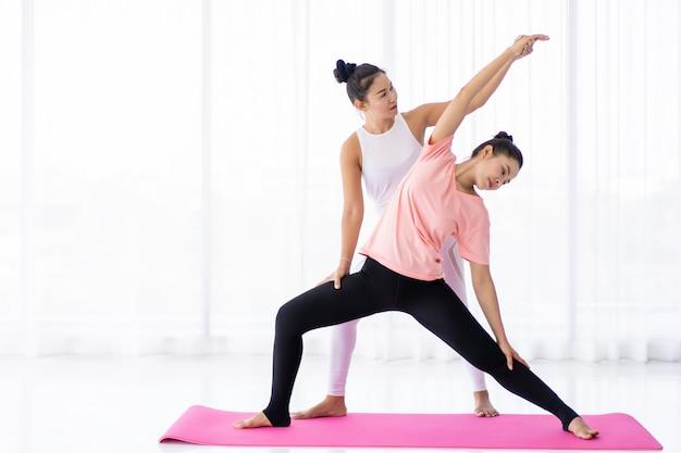 L'yoga di pratica della donna asiatica in buona salute due si esercita insieme nella palestra dell'interno