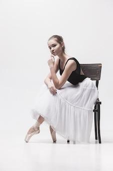 La ballerina adolescente in confezione bianca seduta sulla sedia
