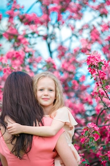 La bambina adorabile con la giovane madre in ciliegia di fioritura fa il giardinaggio il giorno di molla