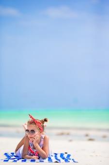 La bambina adorabile gode delle vacanze estive della spiaggia
